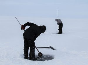 Participants Chiseling Holes with Tuuk and Pauti to Remove Ice - PMC Renewal